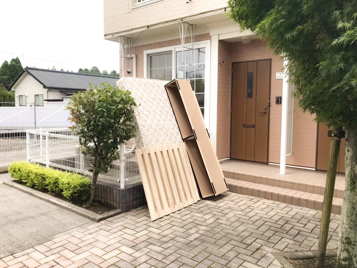 戸別回収のため玄関に搬出されたベッドフレームとマットレス