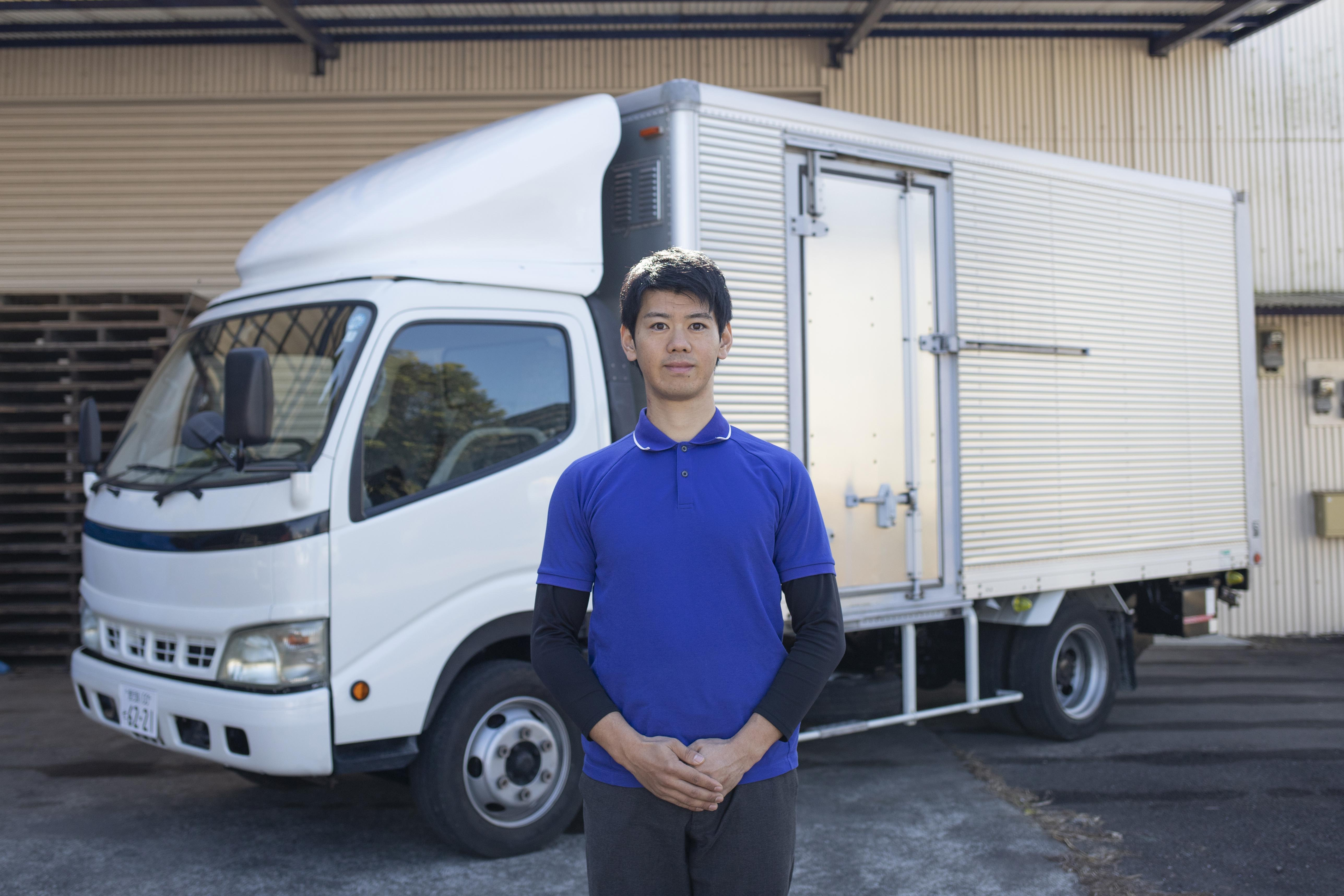 トラックの前に立つ松本